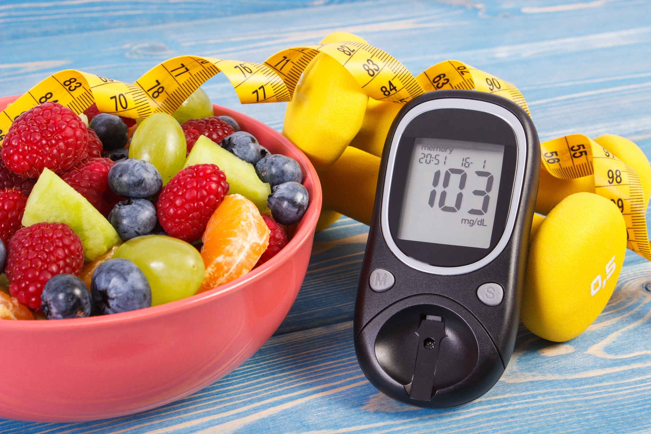 Fruit salad, glucose meter, centimeter and dumbbells, diabetes, healthy lifestyle and nutrition concept