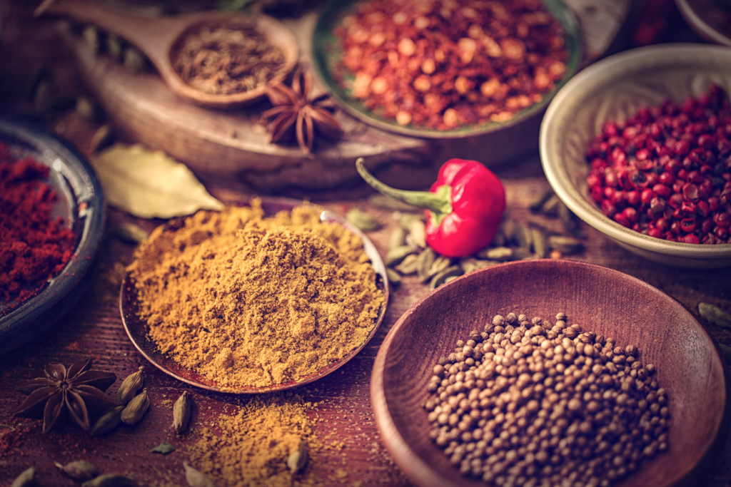 Variation of Spices and Herbs like chili peppers, parsley, rosemary, peppercorns, cayenne pepper, tumeric, cumin, garlic and ginger on wooden background