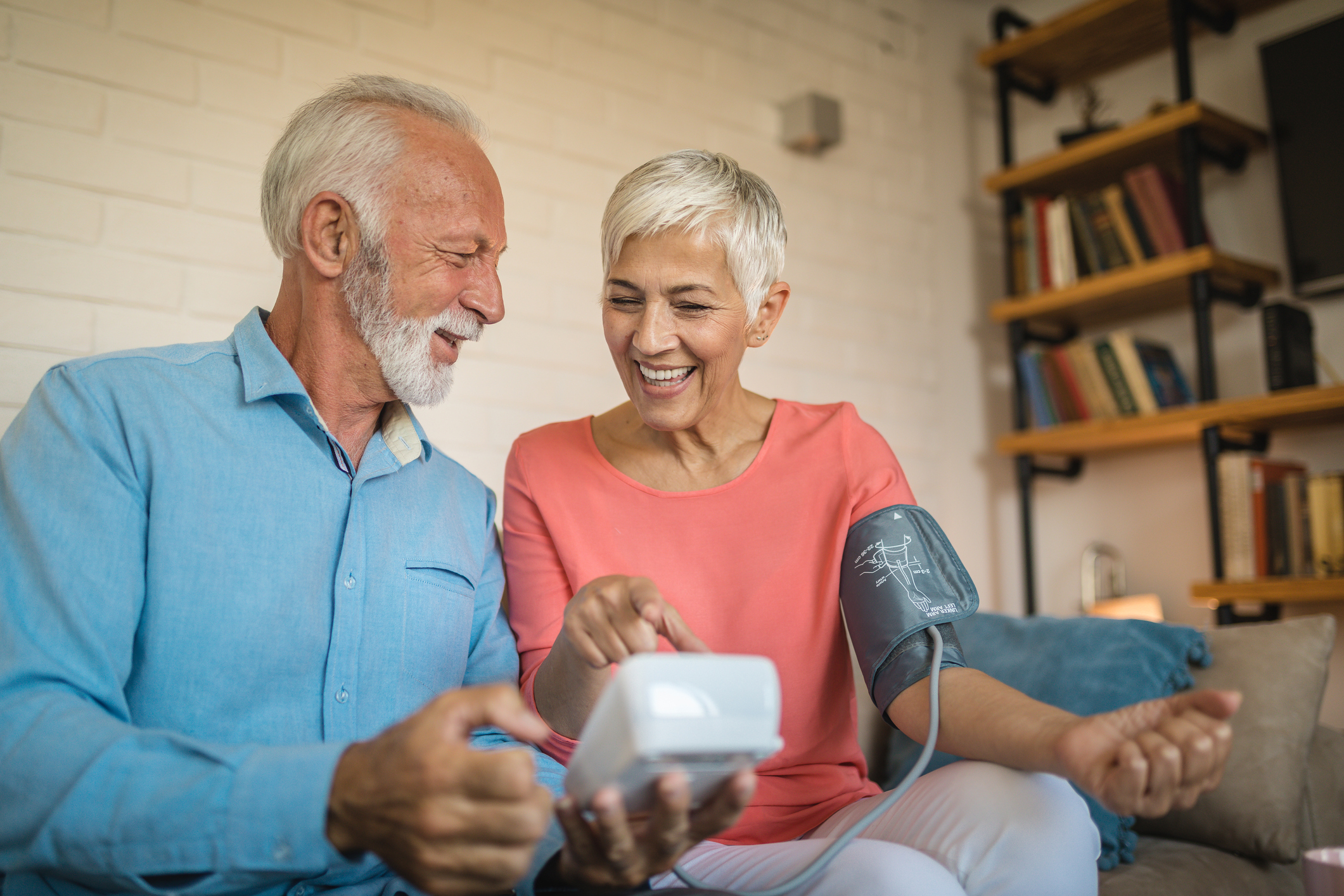 Lovely and cheerful looking senior couple measuring blood pressure to one another at home.