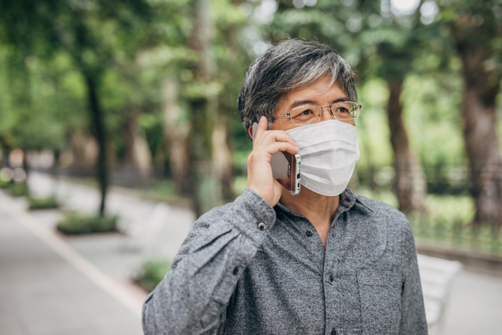 One man, mature man with surgical mask talking on mobile phone downtown in city.